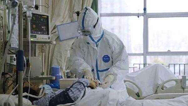 Врач в защитном костюме у постели больного коронавирусом 2019-nCoV в Центральном госпитале города Ухань, Китай (23 января 2020). - Sputnik Армения