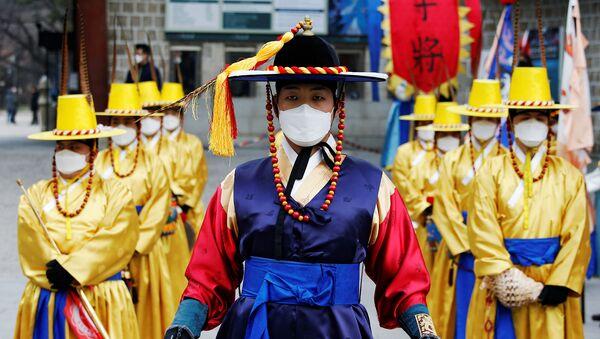 Рабочие в корейских традиционных костюмах и защитных масках во время реконструкции церемонии смены Королевской гвардии перед Дворцом Деоксу (31 января 2020). Сеул - Sputnik Армения