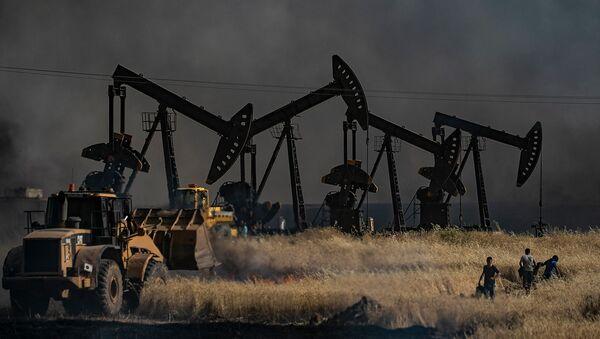 Люди сражаются с огнем рядом с нефтяной скважиной на сельскохозяйственном поле в городе Аль-Кахтания недалеко от сирийско-турецкой границы (10 июня 2019). Сирия - Sputnik Армения