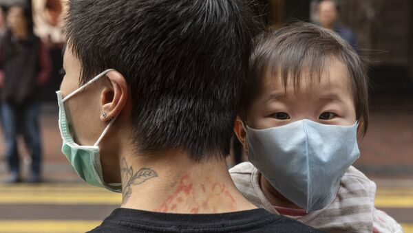 Ребенок в защитной маске на руках отца на одной из улиц в Гонконге. - Sputnik Армения