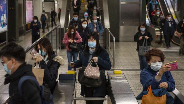 Пассажиры в защитных масках на станции метро в Гонконге. - Sputnik Армения