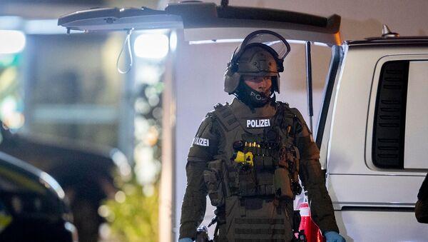 Офицер спецназа охраняет дорогу перед домом, который обыскивает полиция в Ханау после стрельбы в кальянной, где были убиты 8 человек (19 февраля 2020). Германия - Sputnik Армения