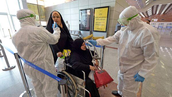 Медицинский персонал проверяет пассажиров в Международном аэропорту Наджаф после того как Иран объявил о случаях заражения коронавирусом в Исламской Республике (21 февраля 2020).  - Sputnik Армения