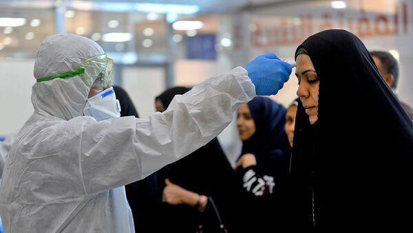 Медицинский персонал проверяет пассажиров в Международном аэропорту Наджаф после того как Иран объявил о случаях заражения коронавирусом в Исламской Республике (21 февраля 2020). - Sputnik Արմենիա