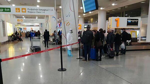 Сотрудник Минздрава в спецодежда встречает пассажиров из Ирана - Sputnik Армения