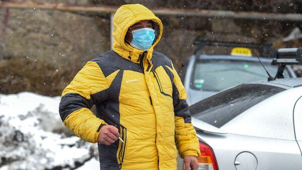 Мужчина на закрытом перекрестке, ведущим к отелю Golden Palace (1 марта 2020). Цахкадзор - Sputnik Армения