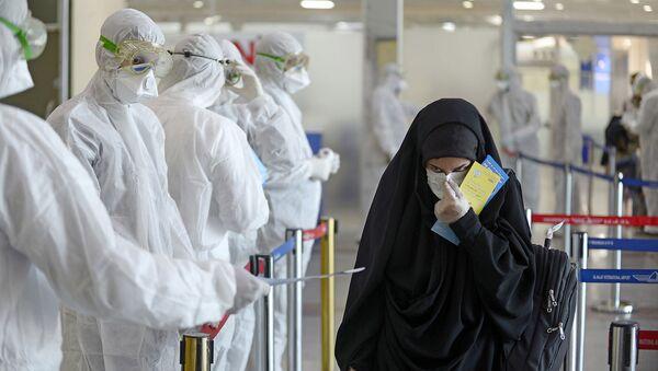 Медицинский персонал измеряет температуру пассажиров, возвращающихся из Ирана в международном аэропорту Наджаф (5 марта 2020). Ирак - Sputnik Արմենիա