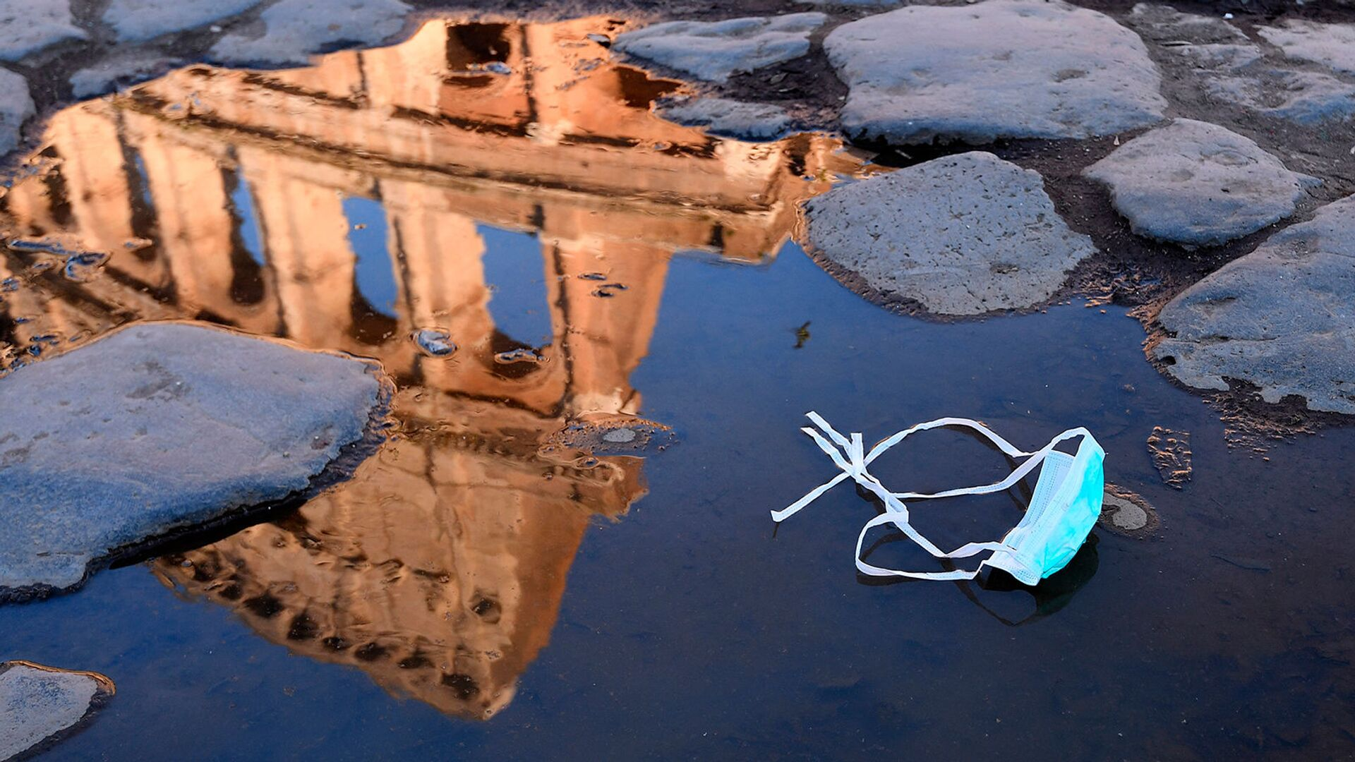 Отраженный в луже Колизей, который будет закрыт после принятия правительством новых мер по предотвращению массовых собраний (8 марта 2020). Рим - Sputnik Армения, 1920, 27.09.2021