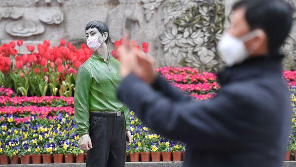 Мужчина фотографирует статую в защитной маске, Пекин - Sputnik Армения