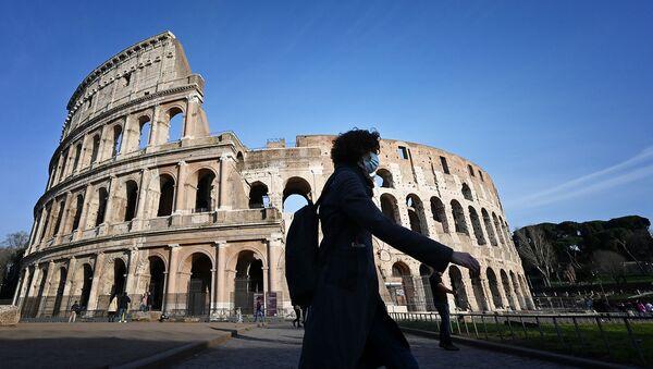 Прохожий в респираторной маске проходит мимо закрытого Колизея (10 марта 2020). Рим - Sputnik Армения