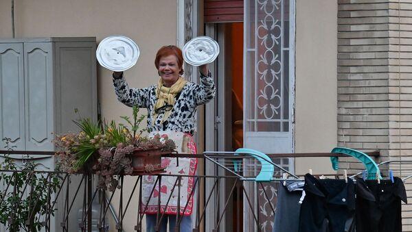 Жительница музицирует на крышках от кастрюль во время флешмоба, запущенного по всей Италии, чтобы собрать людей вместе и попытаться справиться с чрезвычайной ситуацией коронавируса (13 марта 2020). Рим - Sputnik Армения