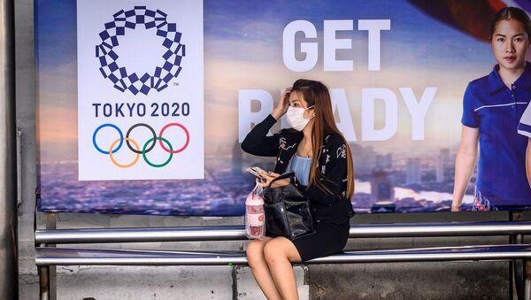 Женщина в защитной маске на автобусной остановке перед рекламой Олимпийских игр Токио-2020 (16 марта 2020). Бангкок - Sputnik Արմենիա