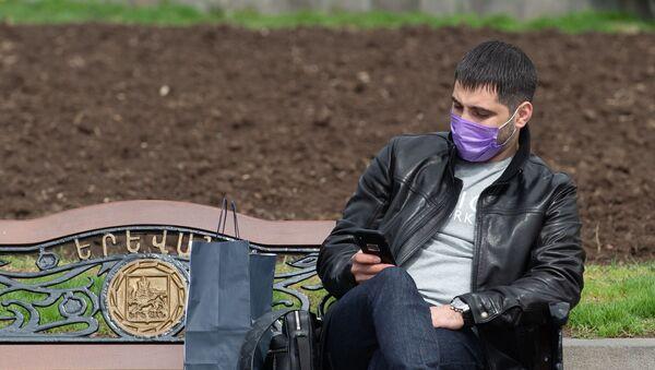 Молодой человек в защитной маске на площади Республики - Sputnik Армения