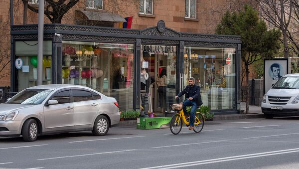 Велосипедист проезжает мимо цветочного магазина на улице Амиряна - Sputnik Армения