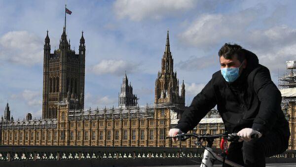 Молодой человек, одетый в защитную маску, едет на велосипеде через Вестминстерский мост (21 марта 2020). Лондон - Sputnik Армения