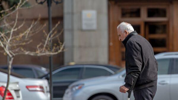 Пожилой человек в защитной маске проходит мимо правительственного здания (30 марта 2020). Еревaн - Sputnik Армения