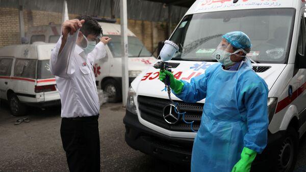 Член экстренного медицинского персонала проходит дезинфекцию после перевода пациента с коронавирусной болезнью (30 марта 2020). Тегеран - Sputnik Армения