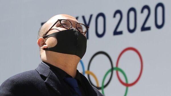 Мужчина в защитной маске проходит перед логотипом токийской Олимпиады (25 марта 2020). Токио - Sputnik Армения