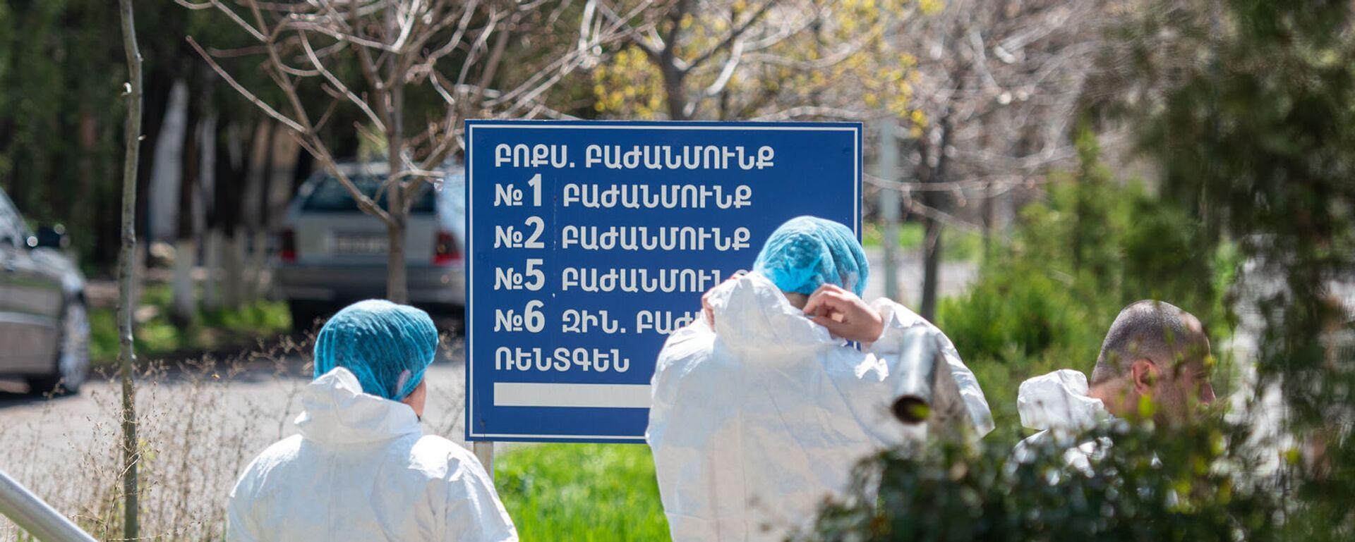 Сотрудники инфекционной больницы Норк около указателя в отделения медцентра - Sputnik Армения, 1920, 07.10.2021