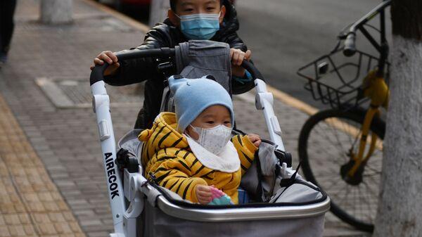 Маленькие дети в защитных масках на одной из улиц Пекина, Китай - Sputnik Армения