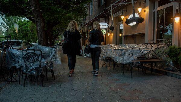 Женщины проходят мимо закрытого кафе на улице Таманяна в Ереване - Sputnik Армения