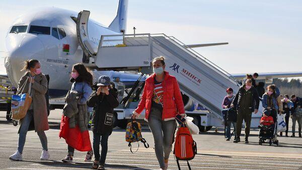 Пассажиры в защитных масках, после карантина в аэропорту Внуково из-за возвращения из стран Азиатско-Тихоокеанского региона, прибывшие в Минск благодаря специальному рейсу Белавиа (20 марта 2020). Минск - Sputnik Արմենիա