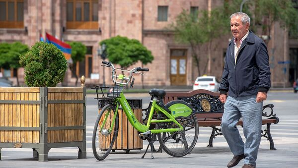 Мужчина проходит мимо велосипеда на площади Республики - Sputnik Արմենիա