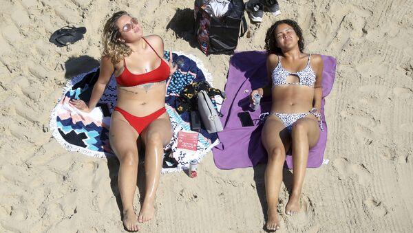 Две загорающие девушки на пляже Каллеркоатс, Англия  - Sputnik Армения