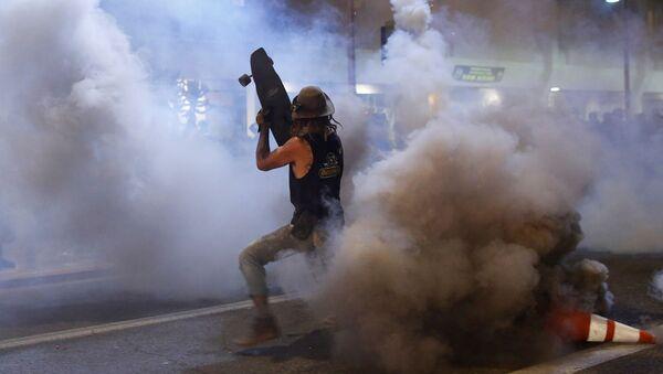 Протестующий прикрывается скейтбордом от слезоточивого газа во время демонстрации в связи со смертью Джорджа Флойда, убитого полицейским (29 мая 2020). Миннеаполис - Sputnik Армения