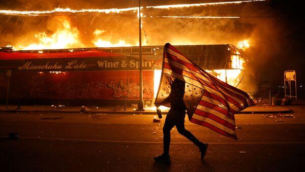 Протестующий с перевернутым флагом США во время демонстрации в связи со смертью Джорджа Флойда, убитого полицейским (28 мая 2020). Миннеаполис - Sputnik Армения