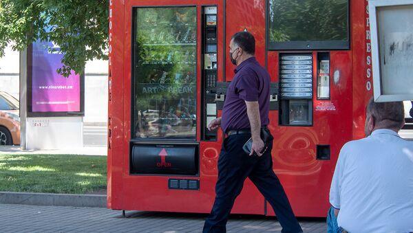 Мужчина в маске проходит мимо торгового аппарата в Ереване - Sputnik Армения
