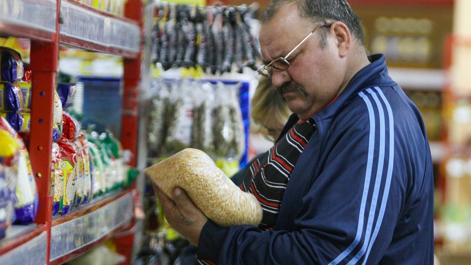 Покупатель у прилавка с крупами в супермаркете - Sputnik Արմենիա, 1920, 03.08.2021
