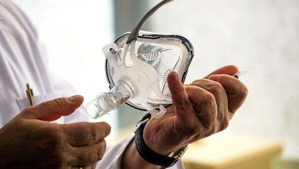 Врач держит в руках маску для искусственной вентиляции легких в палате госпиталя ветеранов войн в Иркутске - Sputnik Армения