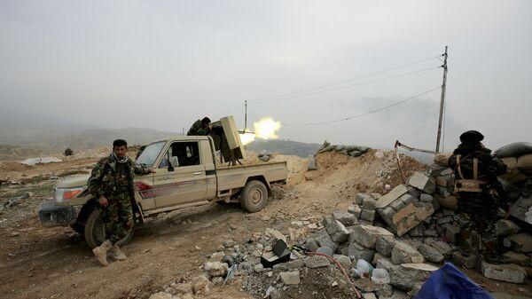 Курдский боец пешмерга стреляет из оружия по позициям группировки Исламского государства неподалеку от города Синджар (29 января 2015). Ирак - Sputnik Армения