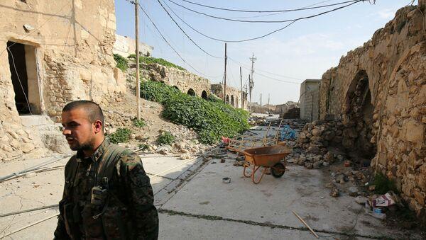 Боец езидов из базирующихся в Сирии Народных подразделений защиты, более известных как YPG, идет по разрушенным улицам Синджара (29 января 2015). Ирак - Sputnik Армения