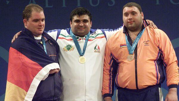 Тяжелоатлеты из Ирана Хосейн Резазаде (в центре), Германии Ронни Веллер (слева) и Армении Ашот Даниелян на пьедестале почета в весовой категории 105 кг XXVII летних Олимпийских игр (26 сентября 2000). Сидней - Sputnik Արմենիա