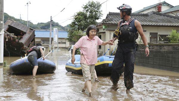 Спасатель помогает женщине во время эвакуации в японской префектуре Кумамото - Sputnik Армения
